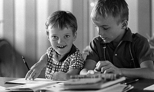 Das Foto zeigt ein Mädchen und einen Jungen im Schulalter, die an einem Schreibtisch sitzen und Lehrmaterial vor sich liegen haben. Das Mädchen hat Contergan und hält einen Füller in seiner rechten Hand.