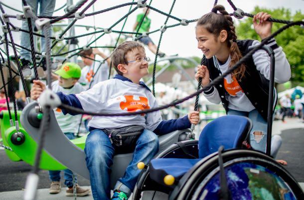 Das Foto zeigt zwei lachende Kinder auf einem Spielplatz, im Vordergrund steht ein Rollstuhl.