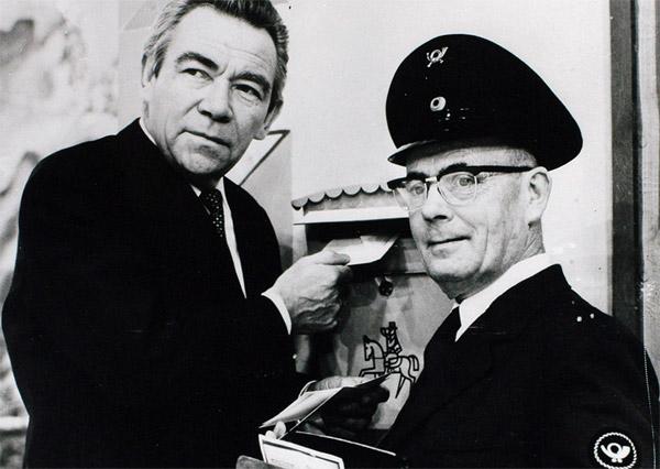 Peter Frankenfeld, damals Moderator der ZDF-Sendung Vergissmeinnicht, wirft einen Brief in einen Briefkasten. Neben ihm steht ein Mann in Post-Uniform.