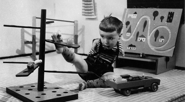 Ein kleiner Junge mit Contergan spielt mit einem Holzkarussell. Er bedient das Rad mit seinem rechten Fuß.