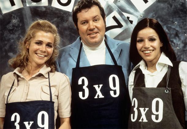 """Das Gruppenbild zeigt ZDF-Moderator Wim Thoelke mit zwei Assistentinnen. Alle drei tragen Schürzen mit der Aufschrift """"drei Mal neun""""."""