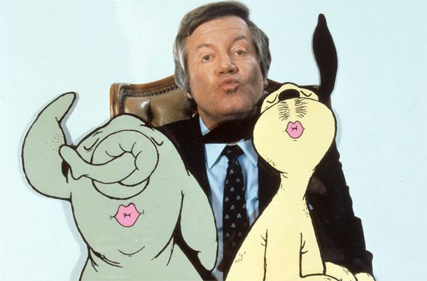 Ein Gruppenbild mit Wim Thoelke und Wum und Wendelin, den beiden Zeichentrickfiguren. Alle drei zeigen dem Betrachter einen Kussmund.