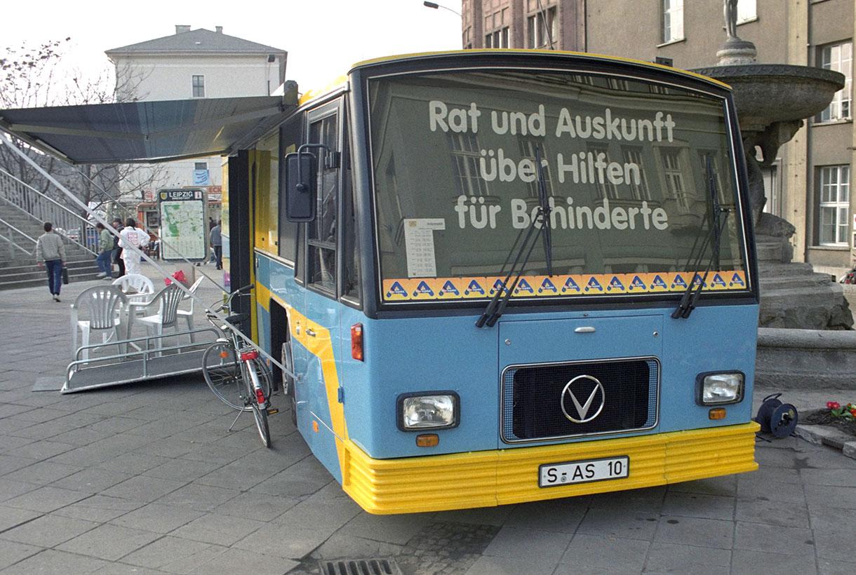 """Ein großer, blau-gelber Reisebus steht auf der Straße. Er ist zu einem Infostand umfunktioniert und hat beide Seitenteile ausgeklappt. Auf der Windschutzscheibe steht """"Rat und Auskunft über Hilfen für Behinderte""""."""