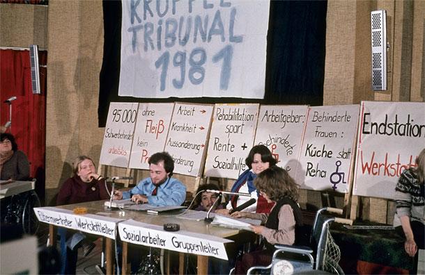 """Fünf Männer und Frauen vom Krüppeltribunal sitzen in ihren Rollstühlen hinter einem langen Tisch mit Mikrofonen. An der Wand dahinter hängen viele Plakate mit Parolen. Auf einem steht """"Behinderte Frauen: Küche statt Reha!"""""""
