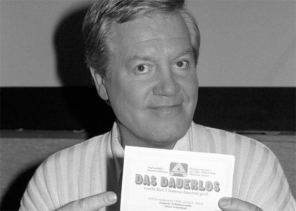 Wim Thoelke lächelt freundlich in die Kamera und deutet mit seinem Zeigefinger auf das damals neue Dauerlos.
