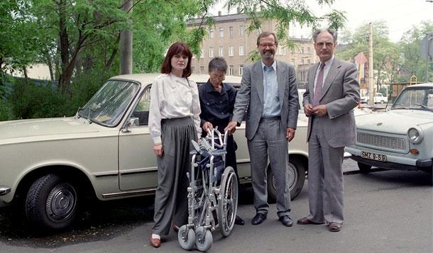 Die Szene zeigt ein Gruppenbild auf offener Straße in der DDR. Vor einem Auto der Marke Wartburg und einem Trabbi stehen zwei Männer und zwei Frauen als Vertreterinnen und Vertreter der Behindertenhilfe Ost und West. Vor einer Frau steht ein zusammengeklappter Rollstuhl.
