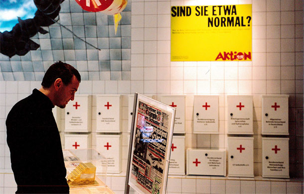 Ein Besucher der Ausstellung betrachtet eine Informationstafel oder ein Exponat. Auf einem knallgelben Aktion-Mensch-Plakat dahinter wird die Frage gestellt: Sind Sie etwa normal?