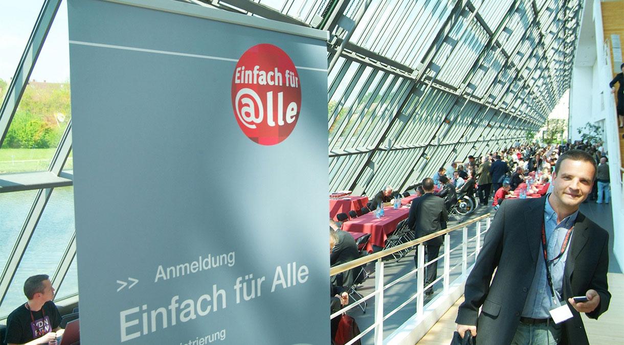 """Die Szene aus der Tagung zur Initiative """"Einfach für alle"""" zeigt links ein Hinweisschild zur Anmeldung. Und rechts eine freundlich lächelnden Besucher der Veranstaltung."""
