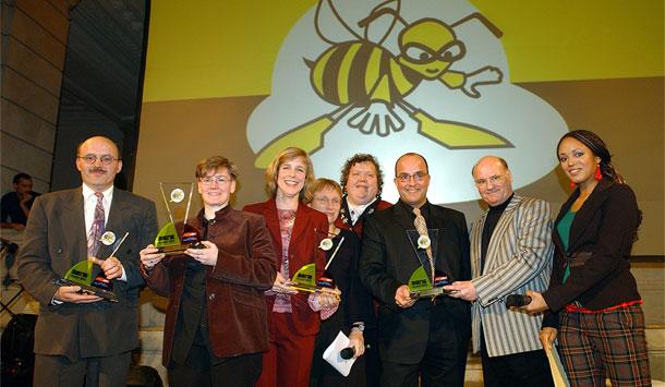 """Das Gruppenfoto stellt die acht Gewinner der """"BIENE"""" im Jahr 2003 vor. Sie stehen auf einer Bühne und halten ihren Preis in Händen. Hinter ihnen hängt das schwarz-gelbe Log der BIENE."""