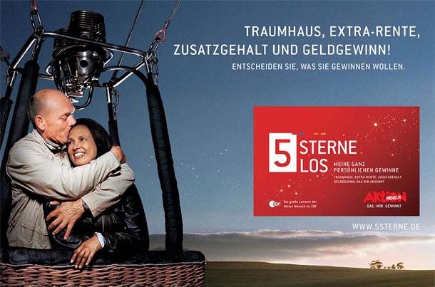 Ein Werbefoto für das 5 Sterne-Los zeigt ein älteres Paar im Korb eines Heißluftballons. Der Mann küsst die Frau auf den Kopf. Vor der Weite einer Landschaft und dem Abendhimmel schwebt das neue rote Los.