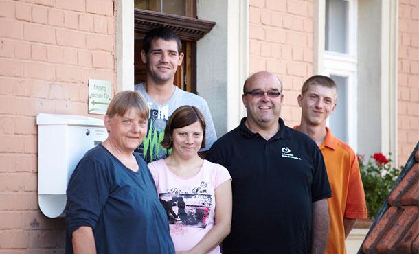 Fünf ganz unterschiedliche Personen stehen vor einer geöffneten Haustür. Die drei Männer und beiden Frauen sind Bewohner eines Wohnprojektes, das die Aktion Mensch gefördert hat.