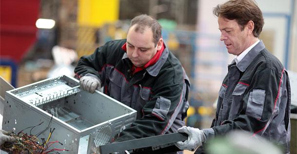 Das Foto zeigt den neuen Aktion Mensch-Botschafter Rudi Cerne und einen Mitarbeiter mit Behinderung in einem geförderten Integrationsprojekt. Sie tragen dicke Arbeitshandschuhe und sortieren Schrott.